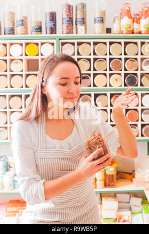Woman smells the aroma of cinnamon in the glass jar - Stock Photo