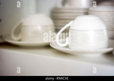 decorated coffee cups kept in a shelf of a white pantry. Interior shot - Stock Photo