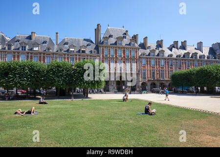 PARIS, FRANCE - JULY 6, 2018: Place des Vosges with ancient buildings and people on the grass in a sunny summer day, clear blue sky in Paris
