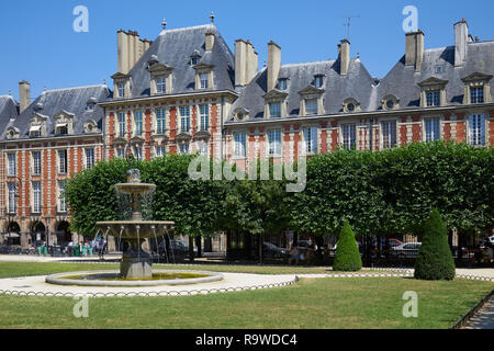 Place des Vosges, red facade buildings and garden in Paris in a sunny summer day, clear blue sky