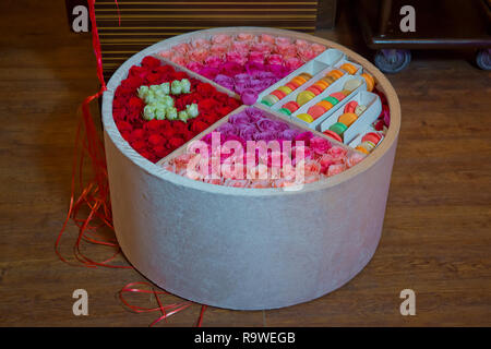 Colorful macarons cake . Paper Box with french dessert - macaroons on gray concrete table with festive decoration. Red and purple flowers - Stock Photo