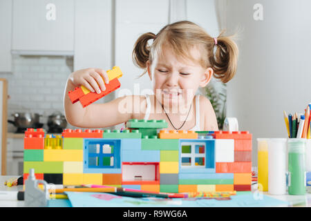 Charming preschooler playing with doll house constructor. Little girl playing with connecting toy cubes - Stock Photo