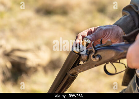 Hunter equips the retro double-barreled shotgun with cartridges, close up. Hunting season. - Stock Photo