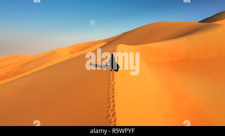 Aerial view from a drone flying next to a woman in abaya (United Arab Emirates traditional dress) walking on the dunes in the desert of the Empty Quar - Stock Photo