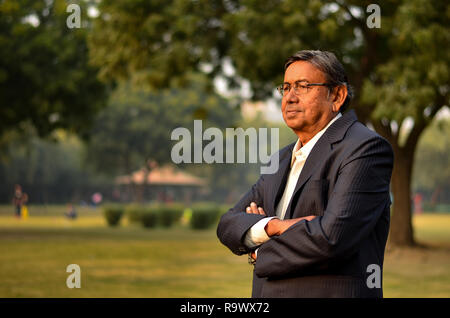 Happy senior Indian man wearing a suit in the outside setting standing and smiling in a park in Delhi, India - Stock Photo