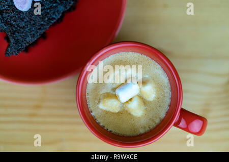 Red ceramic cup of coffee with marshmallow in dense foam served with chocolate cake on a plate, viewed from above on wooden table surface - Stock Photo
