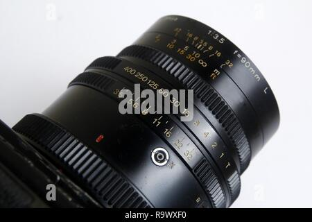 Close up shot of the shutterspeed and aperture ring on the leaf shutter lens of a vintage medium format film camera. - Stock Photo