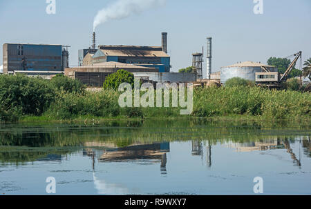 View across large river Nile in Egypt through rural landscape with indutrial sugar cane factory causing pollution - Stock Photo