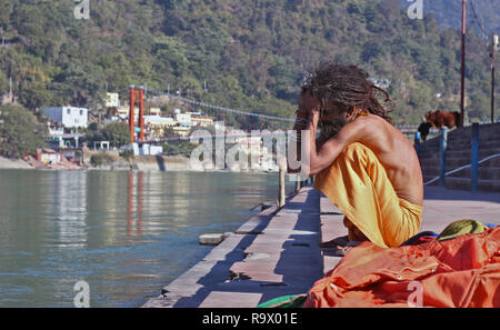 A Young Naga Sadhu with Skinny Body and Dreadlocked Hair sitting on the Bank of Holy River Ganges in Rishikesh, Uttarakhand, India - Stock Photo