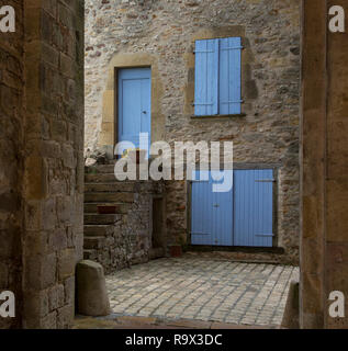 Puycelsi, one of the 100 most beautiful villages in France. A patio with facade, shutters, door and steps - Stock Photo