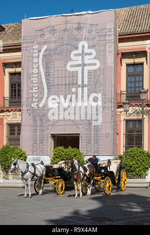 Popular tourist spot with horse drawn carriages in Plaza Virgen de los Reyes, Seville, Spain - Stock Photo