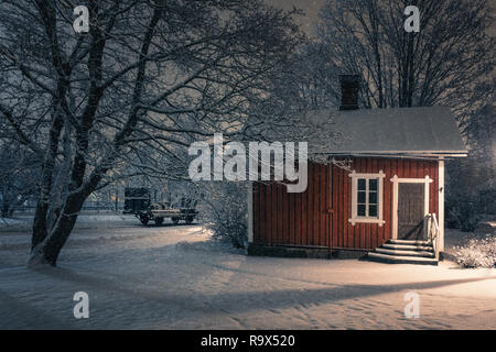 Public cozy old cafe place with snow mood at winter evening in Finland. Light snowflakes. This place is open only in summer time. - Stock Photo
