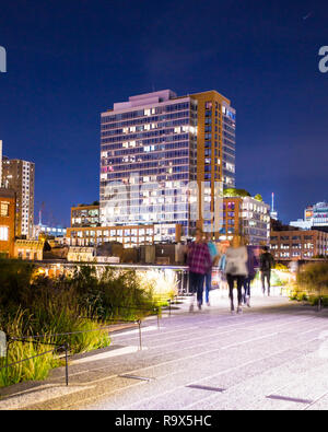 NEW YORK CITY - OCTOBER 21, 2017: Night scene along Highline Park in NYC Manhattan with buildings and the blur of people walking. - Stock Photo