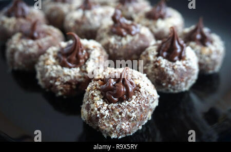 Chocolate delicious homemade praline decorated with grated hazelnut on the black plate
