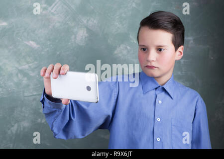 Technology lifestyle concept - teenager boy holding and using his smartphone device to network, browse on-line and making photographs on green grange  - Stock Photo