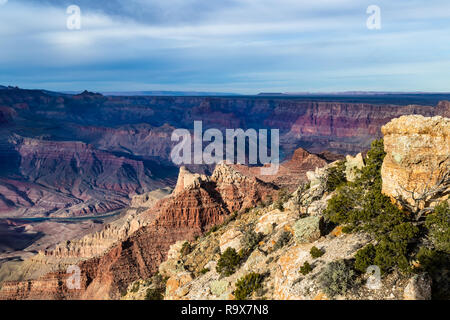 Grand Canyon view at sunset from Lipan Point, South Rim. Hill with rocks and plants in foreground; North rim, colorful canyon and river are in the dis - Stock Photo
