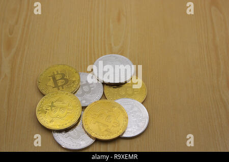 An image of a bunch of gold and silver coins of bitcoins on a wooden table with space to place texts (copy space) - Stock Photo