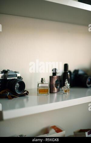 four perfume bottles on a white shelf - Stock Photo