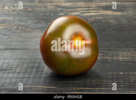 Fresh kumato tomato on dark table closeup - Stock Photo