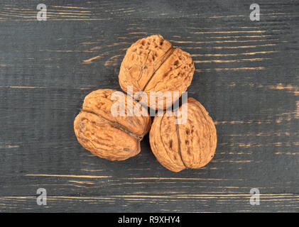 Three dry walnuts on wooden background, top view - Stock Photo