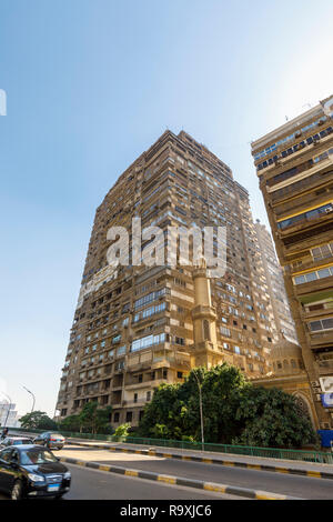 Street scene in Giza, Cairo, Egypt, typical large roadside residential apartment block with external air-conditioning units and a small mosque minaret - Stock Photo