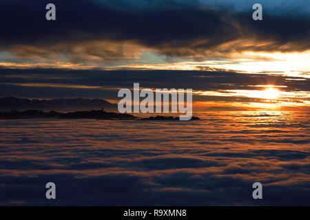 View from Bantiger close to Berne. The cities all lie in the winter fog while some hills stick out. Late sunset. - Stock Photo