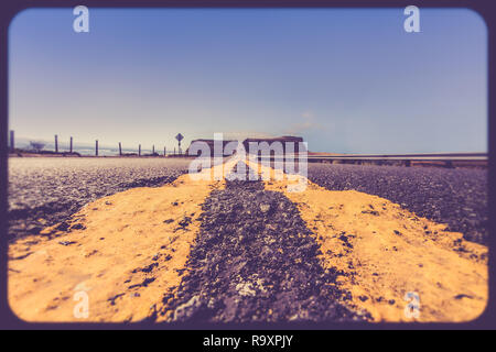Yellow road dividing lines on rugged road along the California coast with vintage retro filter effect - Stock Photo