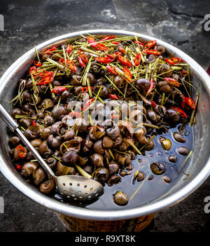 Large bowl of snails served in Vietnam as a delicacy. - Stock Photo