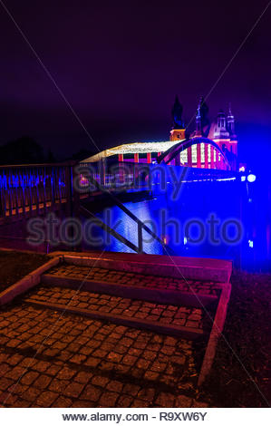 Poznan, Poland - December 26, 2018: Steps and handrail in front of the Warta river with Jordan bridge and cathedral in the background by night. - Stock Photo