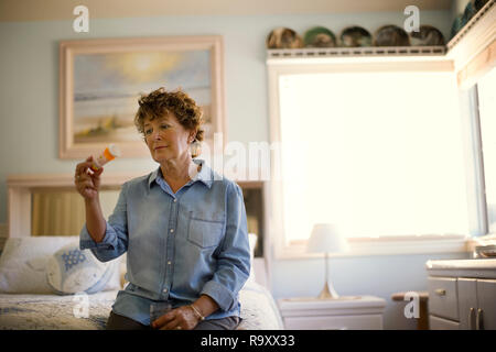 Mature woman reads the instructions on the bottle before taking her medication. - Stock Photo