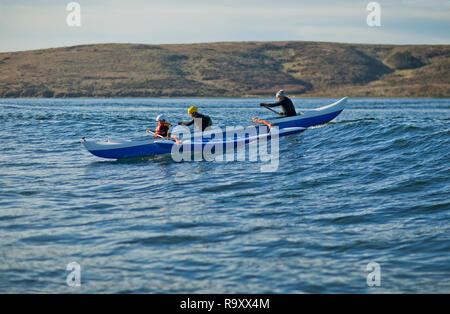 Father and his two sons have fun together paddling a canoe in the ocean. - Stock Photo