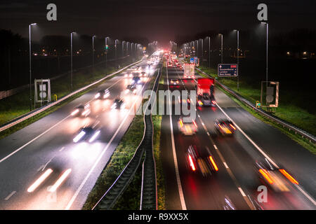 Rush hour traffic shot from above over a busy road showing streaking trails of light of blurred cars at the A44 near Amsterdam - Den Haag. - Stock Photo