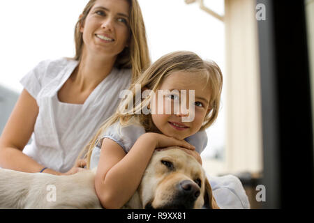 Little girl and her smiling mother relax on the floor with their sleepy dog. - Stock Photo