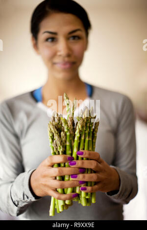 Portrait of a young woman holding a bunch of fresh asparagus. - Stock Photo