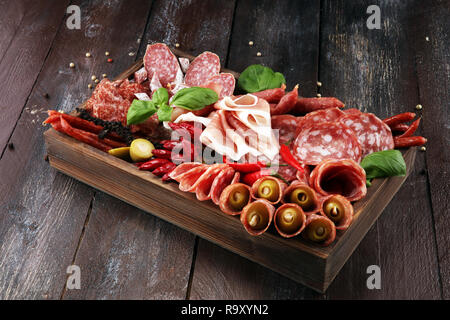 Food tray with delicious salami, pieces of sliced prosciutto crudo, sausage and basil. Meat platter with selection. - Stock Photo