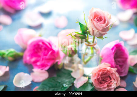 Glass bottles with pink peony roses on a light background with copy space. Feminine header with petals and flowers in pastel tones - Stock Photo