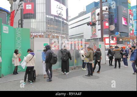 People smoke at designated smoking area in Shibuya Tokyo Japan. - Stock Photo
