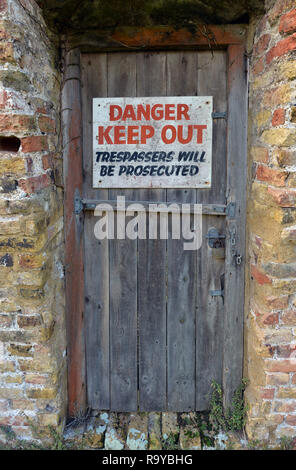 Danger, Keep Out sign on old wooden door. - Stock Photo