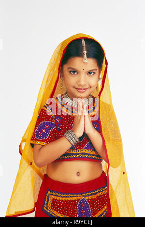 PORTRAIT OF A YOUNG GIRL FROM GUJARAT IN TRADITIONAL COSTUME DOING NAMASTE - Stock Photo
