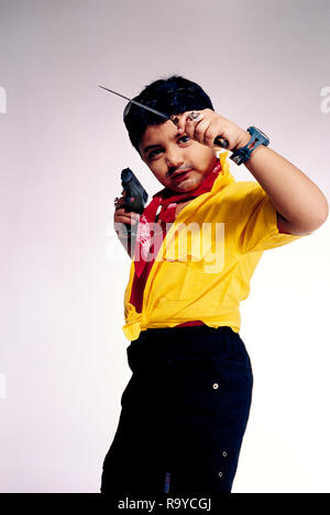 GOONDACriminal.Young boy acting like a typical criminal dressed in garish clothes and holding a 'Rampuri Knife' and a Gun,  MR#498 - Stock Photo