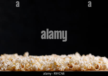 Salted popcorn close-up on a black background. Oscar Film Academy Concept. Snacks and food to watch the movie. - Stock Photo