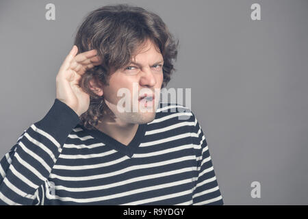 Unhappy hard of hearing man placing hand on ear asking someone to speak up or listening to bad news, isolated on gray background. Negative emotion fac - Stock Photo