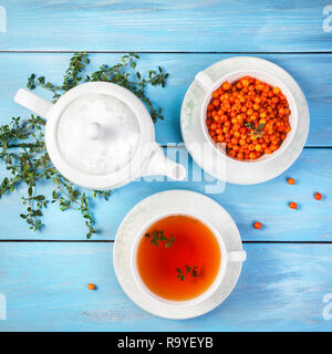 Herbal and berry tea in the cup near teapot and thyme leaves on blue wooden background - Stock Photo