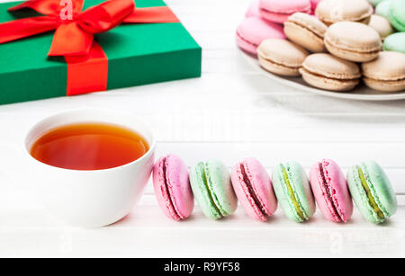 Colorful French macarons near cup of tea and present Christmas box on white background - Stock Photo