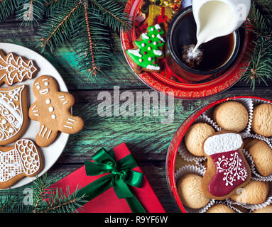 Christmas cookies, red present and cup of coffee with milk on wooden green background - Stock Photo