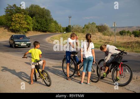 30.08.2016, Causeni, Rajon Causeni, Republik Moldau - Kinder mit Fahrraedern an einer Landtrasse schlagen die Zeit tot. 00A160830D441CARO.JPG [MODEL R - Stock Photo