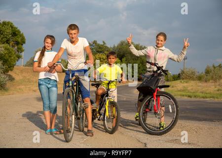 30.08.2016, Causeni, Rajon Causeni, Republik Moldau - Kinder mit Fahrraedern an einer Landtrasse schlagen die Zeit tot. 00A160830D446CARO.JPG [MODEL R - Stock Photo