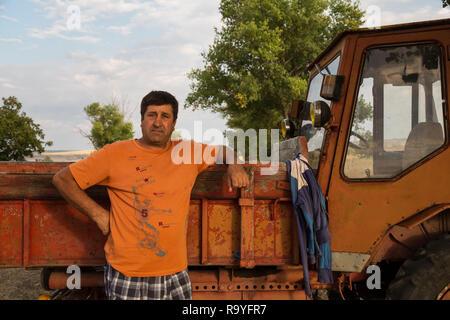 30.08.2016, Causeni, Rajon Causeni, Republik Moldau - Portrait eines Bauern vor seinem Traktor.00A160830D460CARO.JPG [MODEL RELEASE: NO, PROPERTY RELE - Stock Photo