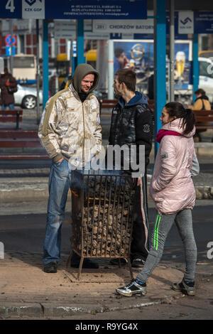 28.02.2018, Bytom (Beuthen), Schlesien, Polen - Menschen an einer Bushaltestelle waermen sich an einem Gefaess mit brennender Steinkohle. 00A180228D13 - Stock Photo