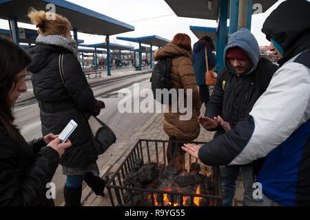 28.02.2018, Bytom (Beuthen), Schlesien, Polen - Menschen an einer Bushaltestelle waermen sich an einem Gefaess mit brennender Steinkohle. 00A180228D14 - Stock Photo
